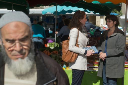 Des partisans du FN distribuent des tracts de campagne sur un marché au Pontet le 9 mars 2017 © BERTRAND LANGLOIS AFP