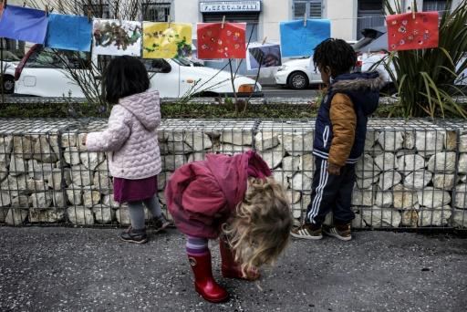 """Des enfants accrochent leurs dessins sur une corde dans le cadre de la """"Grande lessive"""" à Lyon, en France, le 23 mars 2017 © JEFF PACHOUD AFP"""
