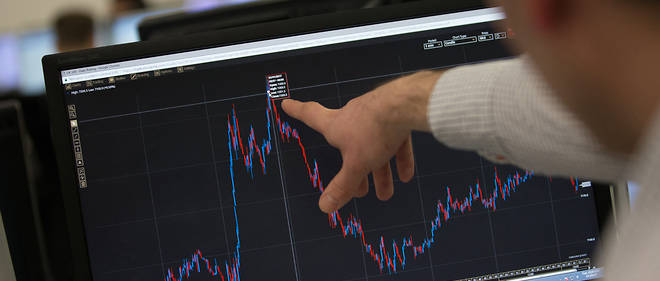 A trader points to a trading screen displaying today's record high for the FTSE 100, at ETX Capital in central London, England on January 3, 2017.London's FTSE 100 reached a historic peak at 7,205.21 points in morning trade, extending a record run seen in the final week of 2016, before easing back from its highs. Since Britain's vote in favour of Brexit, London's FTSE 100 blue-chip index has soared thanks in large part to a weaker pound, even as the economy appears to have shrugged off the impact of the country's impending divorce from the European Union. / AFP PHOTO / Daniel LEAL-OLIVAS