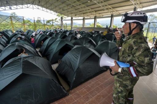 Un soldat colombien donne des instructions à des victimes dans un refuge à Mocoa le 3 avril 2017 © LUIS ROBAYO AFP
