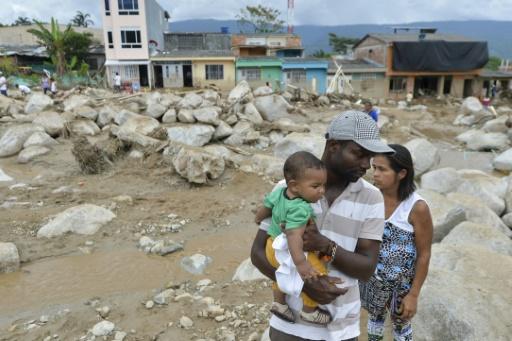 Une famille regarde les dommages causés par la boue à Mocoa, Colombia, le 2 avril 2017 © LUIS ROBAYO AFP