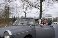 Thierry Dubois à bord de sa voiture de collection.