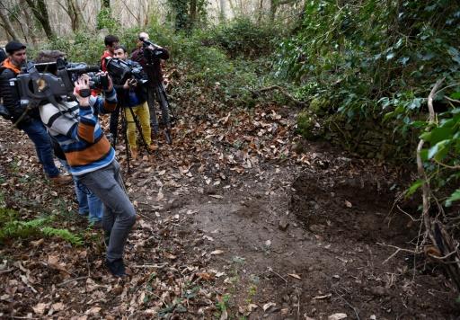 Des journalistes prennent des images d'un trou dans une forêt près de la ville basque espagnole d'Irun où la Guardia civil espagnole a trouvé des explosifs, le 8 mars 2017 © ANDER GILLENEA AFP