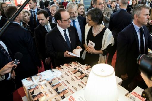 """Le président François Hollande tenant un livre écrit par le candidat du mouvement """"La France insoumise"""" à la présidentielle Jean-Luc Mélenchon, lors de la foire du livre à Paris, le 23 mars 2017 © Etienne LAURENT POOL/AFP/Archives"""