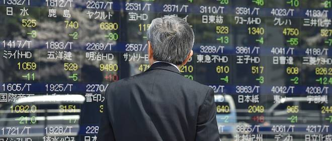 A man looks at an electric quotation board flashing the Nikkei key index of the Tokyo Stock Exchange in Tokyo on April 12, 2017.Tokyo stocks fell April 12 morning as the yen shot to five-month highs against the dollar over fears about growing tensions on the Korean peninsula and in the Middle East. / AFP PHOTO / Kazuhiro NOGI