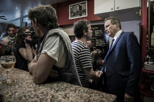 """Nicolas Dupont-Aignan, candidat de """"Debout la France"""" à la présidentielle, discute avec le propriétaire d'un café, le 11 avril 2017 à Paris © PHILIPPE LOPEZ AFP/Archives"""