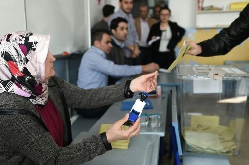 Une membre d'un bureau électoral tend une enveloppe à un votant, lors du référendum turc, le 16 avril 2017 à Istanbul © OZAN KOSE AFP