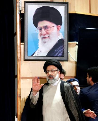 Ebrahim Raissi, candidat à la présidentielle du 19 mai en Iran, marche devant un portrait du guide suprême, l'ayatollah Ali Khamenei  à Téhéran, le 14 avril 2017 © ATTA KENARE AFP
