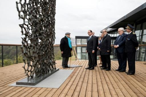 """L'artiste franco-allemand Haim Kern (g), le président Hollande (c) et Jean-Yves Le Drian (3e à droite), se tiennent devant la sculpture baptisée """"Ils n'ont pas choisi leur tombeau"""", à Cerny-en-Laonnois, dans l'Aisne, le 16 avril 2017 © Etienne LAURENT POOL/AFP"""