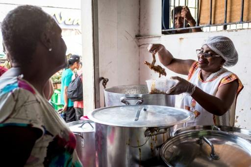 Une femme vend de l'Awara, un plat traditionnel uniquement cuisiné à Pâques, le 15 avril 2017 à Cayenne, en Guyane © jody amiet AFP
