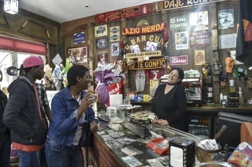 Bangali (g), originaire du Senegal, et Annabel, originaire du Niger, rient avec la serveuse d'un bar de Sant' Alessio in Aspromonte dans le sud de l'Italie, le 6 avril 2017 © Andreas SOLARO AFP