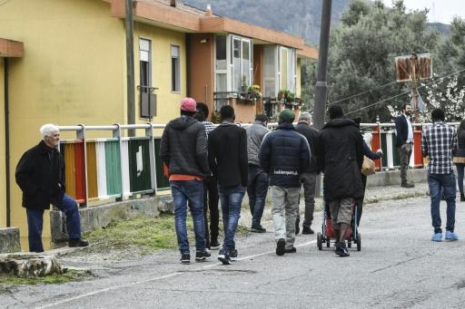 Des habitants du village regardent un groupe de migrants marcher dans les rues de Sant' Alessio in Aspromonte © Andreas SOLARO AFP