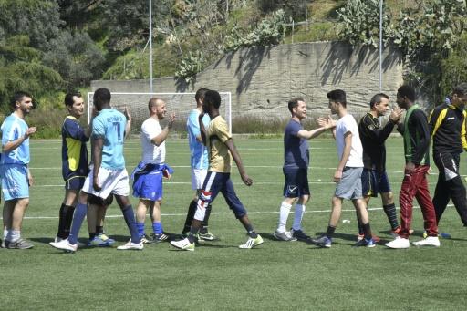 Les joueurs d'une équipe de football locale et des migrants se saluent après un match © Andreas SOLARO AFP
