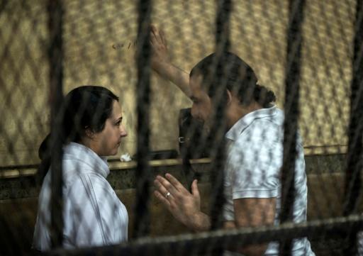 La militante égypto-américaine Aya Hijazi, fondatrice de l'ONG Belady pour les enfants des rues, parle avec son mari dans la cage des accusés, avant le début de son procès au Caire, le 16 avril 2017 © MOHAMED EL-SHAHED AFP