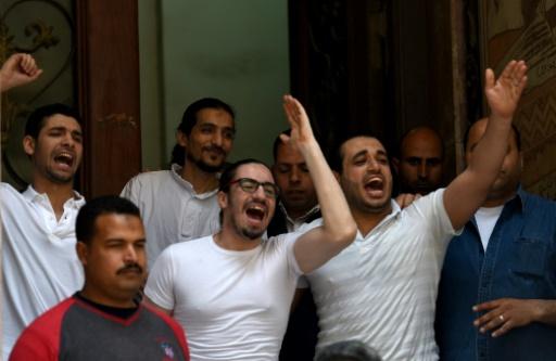 Mohamed Hassane (d), le mari de la militante égypto-américaine Aya Hijazi, et des collègues de travail réagissent à l'annonce de son acquittement, le 16 avril 2017 au Caire © MOHAMED EL-SHAHED AFP