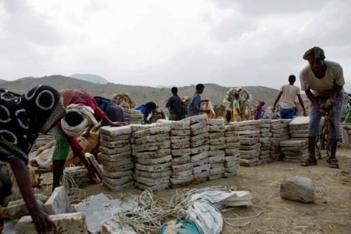 Des hommes déchargent des briques de sel à Berhale, dans la région de la dépression du Danakil, le 27 mars 2017 en Ethiopie © ZACHARIAS ABUBEKER AFP