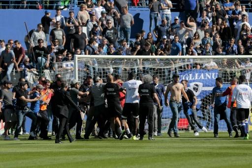 Des supporters bastiais envahissent la pelouse du stade Armand-Cesari pour tenter d'agresser le gardien de Lyon Anthony Lopes (rouge) à l'échauffement, le 16 avril 2017 © PASCAL POCHARD-CASABIANCA AFP