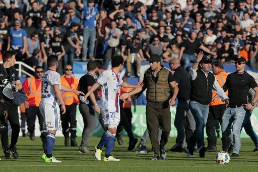 Un membre de l'encadrement bastiais (c-d) échange des mots avec le joueur de Lyon Rafael da Silva (c-g), lors d'échauffourées sur la pelouse du stade Armand Cesari, le 16 avril 2017 à Bastia © PASCAL POCHARD-CASABIANCA AFP