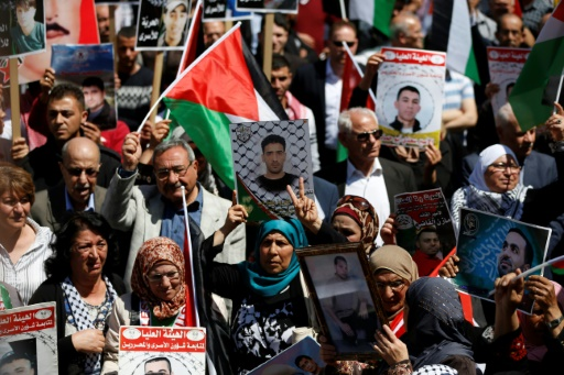 Des manifestants tiennent des photos de détenus palestiniens lors d'un rassemblement à Ramallah, le 17 avril 2017 © ABBAS MOMANI AFP