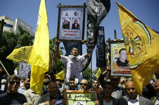 Des manifestants tiennent des photos de détenus palestiniens lors d'un rassemblement, le 17 avril 2017 à Gaza © MOHAMMED ABED AFP