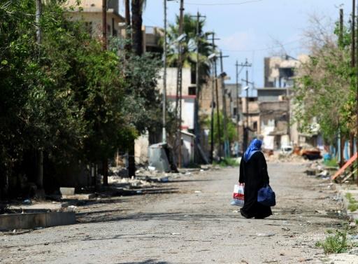 Une femme marche dans une rue de la vieille ville de Mossoul, le 17 avril 2017 © AHMAD AL-RUBAYE AFP