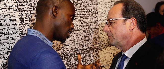 Babacar Mbaye Diouf explique son œuvre au président français, François Hollande, lors de l'inauguration le 13 avril 2017 de l'exposition «Trésors de l'islam en Afrique, de Tombouctou à Zanzibar» à l'Institut du monde arabe jusqu'au 30 juillet 2017.