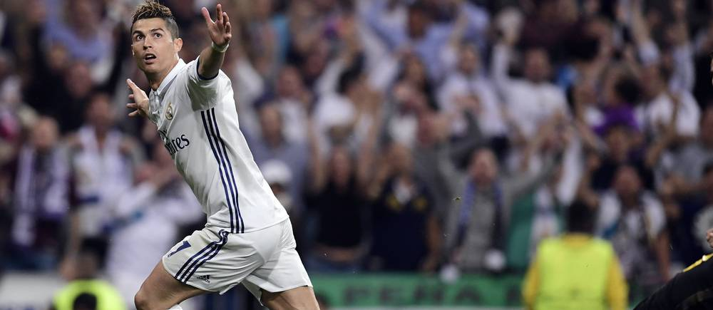 Real Madrid's Portuguese forward Cristiano Ronaldo celebrates his second goal during the UEFA Champions League semifinal first leg football match Real Madrid CF vs Club Atletico de Madrid at the Santiago Bernabeu stadium in Madrid, on May 2, 2017. / AFP PHOTO / JAVIER SORIANO