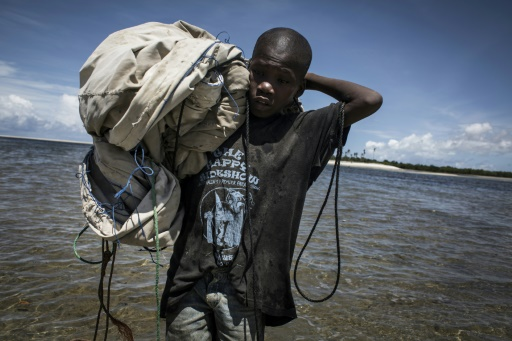 Ce jeune pêcheur Mozambicain regagne la rive sa voile sur l'épaule après une journée de pêche, le 16 février 2017 à Palma  © JOHN WESSELS AFP/Archives