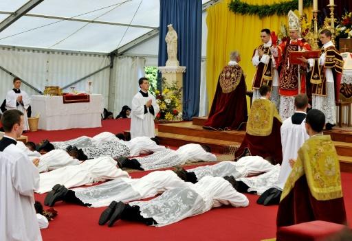 De jeunes prêtres se prosternent et reçoivent la bénédiction de l'évêque Bernard Fellay lors de la messe d'ordination de la Fraternité sacerdotale Saint-Pie X à Econe en Suisse, le 29 juin 2009 © FABRICE COFFRINI AFP