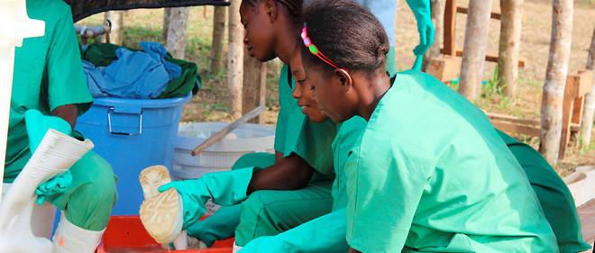 Des secouristes stérilisent leurs habits et leurs chaussures près d'un centre de traitement d'Ebola à Lokolia en octobre 2014.