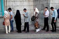 Des Iraniens font la queue devant un bureau de vote de Téhéran vendredi matin pour choisir leur nouveau président. ©BEHROUZ MEHRI
