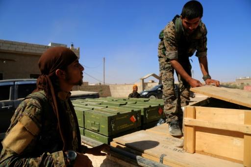 Des Forces démocratiques syriennes (FDS) déchargent des caisses de munitions fournies par la coalition dirigée par les États-Unis, dans un village au nord de Raqa le 7 juin 2017 © DELIL SOULEIMAN AFP