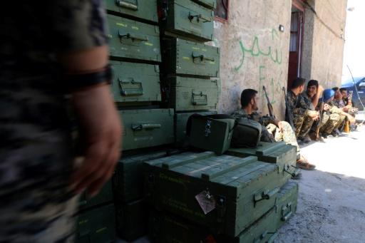 Des Forces démocratiques syriennes (FDS) se reposent après avoir déchargé des caisses de munitions fournies par la coalition dirigée par les États-Unis, dans un village au nord de Raqa le 7 juin 2017 © DELIL SOULEIMAN AFP