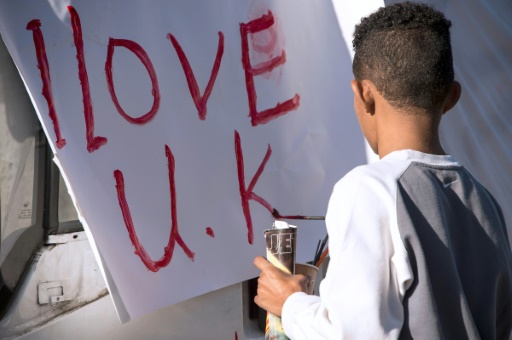 """Un jeune migrant réalise une pancarte, """"j'aime le Royaume-Uni"""", à Calais le 31 octobre 2016 © PHILIPPE HUGUEN AFP/Archives"""