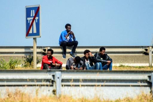 Des migrants sur la route menant au port de Calais le 21 juin 2017 © DENIS CHARLET AFP