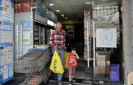 Un réfugié syrien sort d'une boutique qui accepte la carte de débit de l'ONU, le 14 juin 2017 à Beyrouth, au Liban © JOSEPH EID AFP