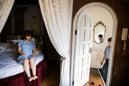 Masayuki Ozaki, kinésithérapeute, entre dans une chambre où Mayu, sa poupée en silicone est installée sur le lit, le 14 juin 2017 à Yachimata, au Japon © Behrouz MEHRI AFP