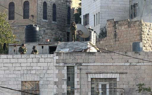 Image d'archives prise le 21 octobre 2015 montrant des membres des forces de sécurité israéliennes sur le toit d'une maison à Hébron pendant des affrontements avec des manifestants palestiniens © HAZEM BADER AFP/Archives