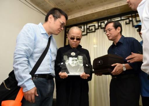 Photographie du Shenyang Municipal Information Office, montrant la femme du dissident chinois Liu Xiaobo, Liu Xia (c) et son frère, Liu Xiaoguang (L), recevant les cendres du défunt après son incinération, le 15 juillet 2015 à Shenyang © Handout Shenyang Municipal Information Office/AFP