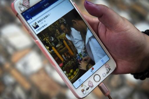 Une scène d'un rituel est diffusée sur le smartphone d'un client de l'ermite Toon, le 20 mai 2017 à Khon Kaen, dans le nord de la Thaïlande  © Lillian SUWANRUMPHA AFP