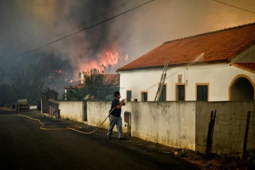 Un habitant arrose le toit de sa maison alors qu'un incendie s'approche de Maçao, le 25 juillet 2017 au Portugal © PATRICIA DE MELO MOREIRA AFP