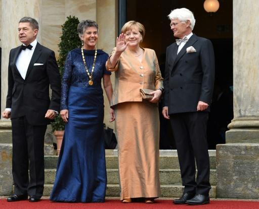 La chancelière allemande Angela Merkel (2e. à g.) et son époux Joachim Sauer (g) accueillis par la mairesse de Bayreuth, Brigitte Merk-Erbe et son mari Thomas Erbe, le 25 juillet 2017 © Christof STACHE AFP