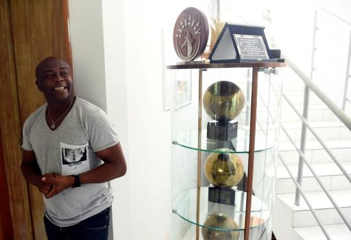 L'ancien footballeur ghanéen Abedi Pelé pose avec ses trophées, dont ses trois Ballons d'or africain, le 13 juillet 2017 chez lui à Accra © PIUS UTOMI EKPEI AFP