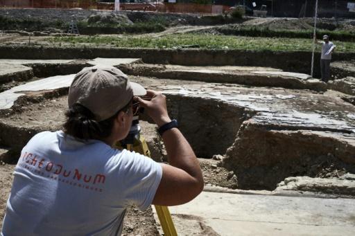 Un archéologue prend des photos d'un site datant de l'époque romaine, le 31 juillet 2017 à Sainte-Colombe, dans le Rhône © JEAN-PHILIPPE KSIAZEK AFP