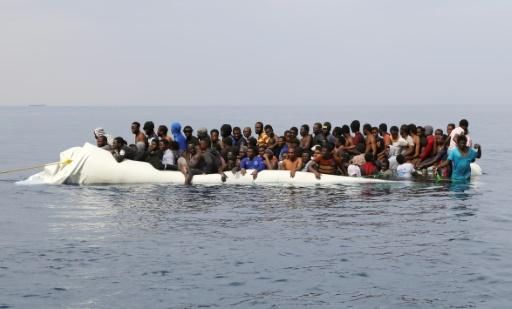 Tandis que leur canot coule, des migrants attendent d'être secourus au large des côtes de Zawiyah en Libye, à l'est de Tripoli, le 20 mars 2017 © Abdullah ELGAMOUDI AFP/Archives