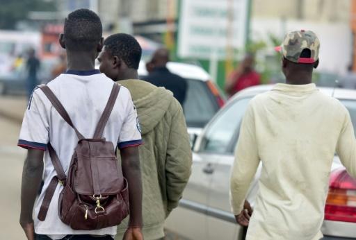 De jeunes hommes marchent dans le quartier populaire d'Abobo, à Abidjan, le 3 août 2017 © ISSOUF SANOGO AFP