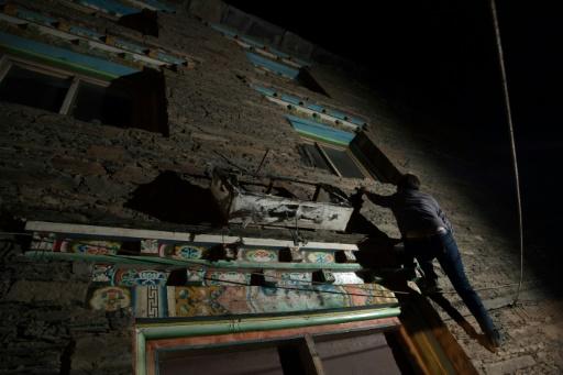 Trinley Norbu, un membre de l'éthnie tibétaine matriarcale des Zhaba, montre comment il grimpe aux murs de la maison de la femme qu'il convoite, le 27 mai 2017 dans la vallée du fleuve Yalong, dans la province chinoise du Sichuan © Johannes EISELE AFP