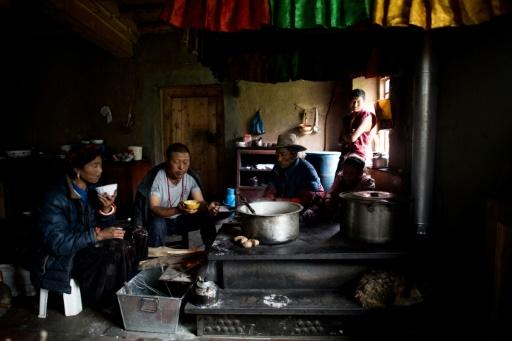 Une femme et sa famille prennent leur petit-déjeuner, constitué notamment de thé et de beurre de yak, le 28 mai 2017, à Zhaba, dans la vallée du fleuve Yalong, dans la province chinoise du Sichuan © Johannes EISELE AFP