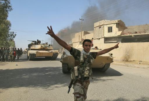 """Un combattant irakien du Hachd al-Chaabi, unités paramilitaires, fait le """"V"""" de la victoire dans Tal Afar, l'un des derniers bastions du groupe Etat islamique (EI) en Irak, le 25 août 2017 © AHMAD AL-RUBAYE AFP"""