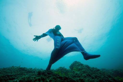 """Amateur de chute libre, Pierre Frolla se jette d'un piton rocheux sous-marin dans son """"Oceanwings"""", sa combinaison en néoprène, au large de Monaco en Méditerranée le 13 août 2017 © BORIS HORVAT AFP"""